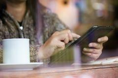 Рука женщины используя цифровую таблетку в кафе в дождливом дне Стоковое Изображение RF