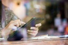 Рука женщины используя цифровую таблетку в кафе в дождливом дне Стоковая Фотография RF