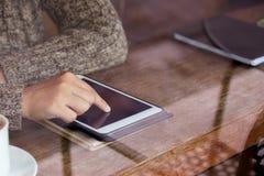 Рука женщины используя цифровую таблетку в кафе в дождливом дне Стоковые Изображения