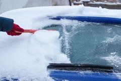Рука женщины используя щетку и извлекает снег от автомобиля и windscreen Стоковые Фотографии RF
