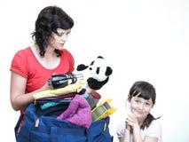 Рука женщины и дочери напихала вполне одежд и сумки плеча Стоковая Фотография