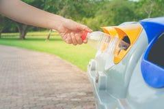Рука женщины кладя используемые пластичные мусорные корзины бутылки публично или сегрегированные ненужные ящики публично паркуют стоковые фото