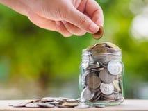 Рука женщины кладя монетку денег в стеклянный опарник для сохраняя денег S стоковые фотографии rf