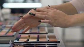 Рука женщины клиента выбирает декоративные косметики от палитры других цветов для модного макияжа и испытания видеоматериал