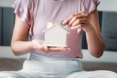 Рука женщины конца-Вверх кладет монетку денег в расквартировывать банк на спальню , Женская рука вводит монетку в сбережения дома стоковое фото