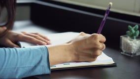Рука женщины крупного плана писать на тетради на таблице, работе девушки с книгой или дневнике дома