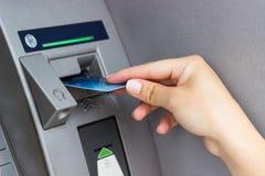 Рука женщины кладет кредитную карточку в ATM стоковое изображение rf
