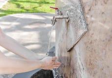 Рука женщины моя с водой от водопроводного крана в парке Стоковые Изображения