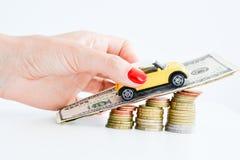 Рука женщины нажимая автомобиль игрушки над стогом монеток Стоковое фото RF