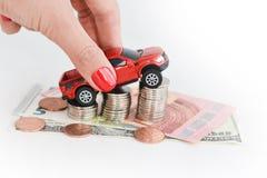 Рука женщины нажимая автомобиль игрушки над стогом монеток Стоковые Фото