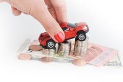 Рука женщины нажимая автомобиль игрушки над стогом монеток Стоковое Фото