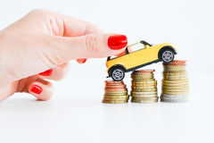 Рука женщины нажимая автомобиль игрушки над стогом монеток Стоковые Фотографии RF