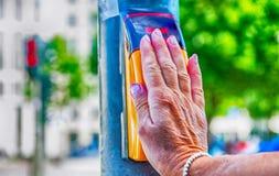 Рука женщины нажимая кнопку crosswalk с городом в backgroun Стоковые Изображения RF