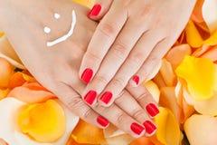 Рука женщины над лепестками цветка Стоковые Фото