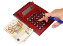 Рука женщины на калькуляторе с деньгами стоковое изображение