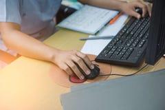 Рука женщины на мыши работая в офисе Стоковое фото RF
