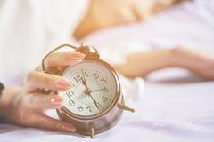 Рука женщины поворачивает будильник просыпая вверх в утре Стоковая Фотография RF