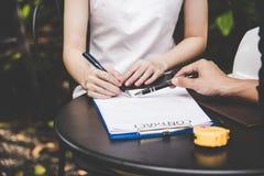 Рука женщины подписывая контракт для строя дома с человеком архитектора Стоковая Фотография