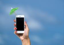 Рука женщины показывая зонтик мобильного телефона и коктеиля на небе Стоковые Изображения
