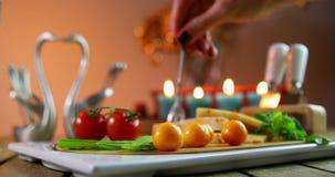 Рука женщины положила вилку в сыр желтый цвет свежих овощей сыра Изолированный на оранжевой предпосылке сток-видео