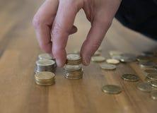 Рука женщины подсчитывая монетки денег Стоковое фото RF