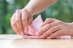 Рука женщины подсчитывая тайские наличные деньги Стоковая Фотография