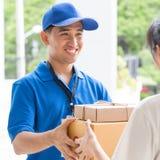 Рука женщины признавая поставку коробок от работника доставляющего покупки на дом Стоковое Изображение