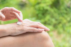 Рука женщины прикладывает лосьон на коже задней руки Стоковая Фотография RF