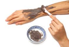 Рука женщины прикладывая сливк глины спы косметическую Стоковые Изображения