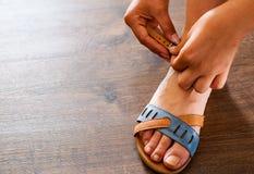 Рука женщины прикрепляет ремень на сандалиях кожаных ботинок Стоковые Фото