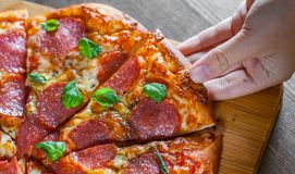 Рука женщины принимает кусок пиццы Pepperoni с сыром моццареллы, салями, томатами, перцем, специями и свежим базиликом Итальянско стоковые изображения