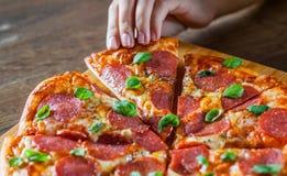 Рука женщины принимает кусок пиццы Pepperoni с сыром моццареллы, салями, томатами, перцем, специями и свежим базиликом Итальянско стоковая фотография