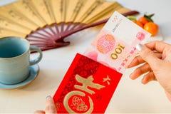 Рука женщины принимая вне 100 юаней от красного конверта Стоковое Фото