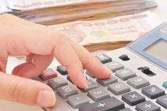 Рука женщины при калькулятор подсчитывая деньги Стоковые Фото