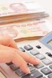 Рука женщины при калькулятор подсчитывая деньги Стоковое Фото