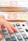 Рука женщины при калькулятор подсчитывая деньги Стоковая Фотография RF