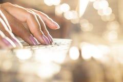 Рука женщины работая на компьтер-книжке компьютера зарабатывая деньги онлайн от дома Стоковая Фотография