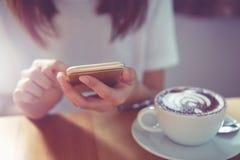 Рука женщины работая с телефоном на столе в кофейне Год сбора винограда к Стоковая Фотография