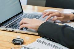 Рука женщины работая с телефоном и компьтер-книжкой на деревянном столе в офисе смогите быть использовано на объявлении Стоковое Фото