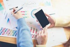 Рука женщины работая с телефоном на деревянном столе в офисе смогите быть использовано на рекламе стоковое изображение rf
