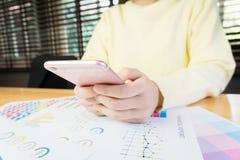Рука женщины работая с телефоном на деревянном столе в офисе смогите быть использовано на рекламе стоковое изображение
