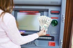 Рука женщины разделяя деньги от внешнего банка ATM Стоковое Фото