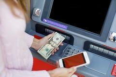 Рука женщины разделяя деньги от внешнего банка ATM Стоковое Изображение