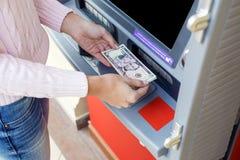 Рука женщины разделяя деньги от внешнего банка ATM Стоковая Фотография RF