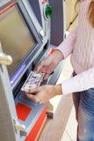 Рука женщины разделяя деньги от внешнего банка ATM Стоковая Фотография