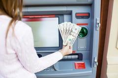 Рука женщины разделяя деньги от внешнего банка ATM Стоковые Изображения RF