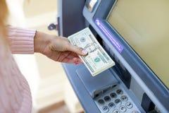 Рука женщины разделяя деньги от внешнего банка ATM Стоковые Фото