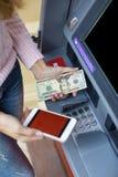 Рука женщины разделяя деньги от внешнего банка ATM Стоковые Изображения