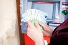 Рука женщины разделяя деньги от внешнего банка ATM Стоковое фото RF