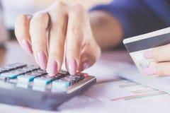Рука женщины рассчитывать калькулятор используя ее кредитную карточку для ходить по магазинам онлайн Стоковое Изображение